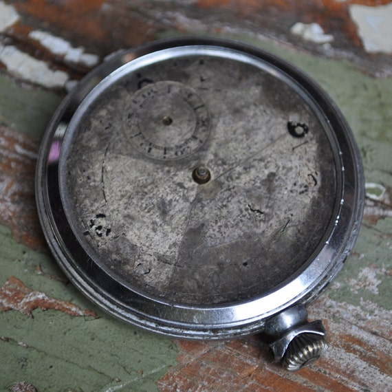 Antique pocket watch case with movement and dial.