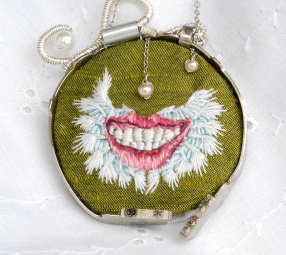 "Green embroidered necklace of a mightily winged smile wrapped in typewriter keys ""Pneumothorax"""