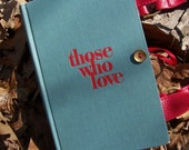 """grey-blue and red book purse titled """"Those Who Love"""""""