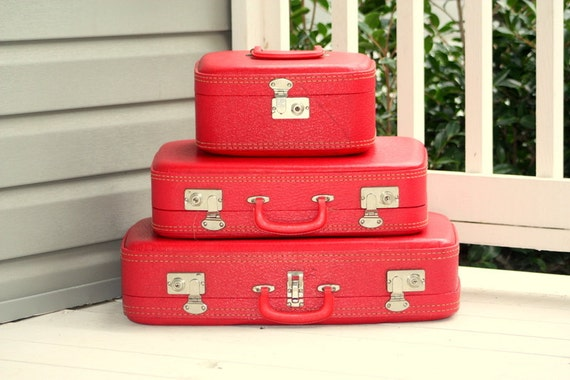1960s 3 piece red retro luggage set. Two Suitcases and makeup case. Plastic exterior, blue cloth interior
