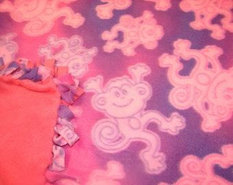 Fleece blanket with pink and purple monkeys on it ,  other side is all rose pink