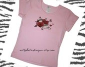 Mom and Dad tattoo hearts and mini hearts on short sleeve light pink shirt