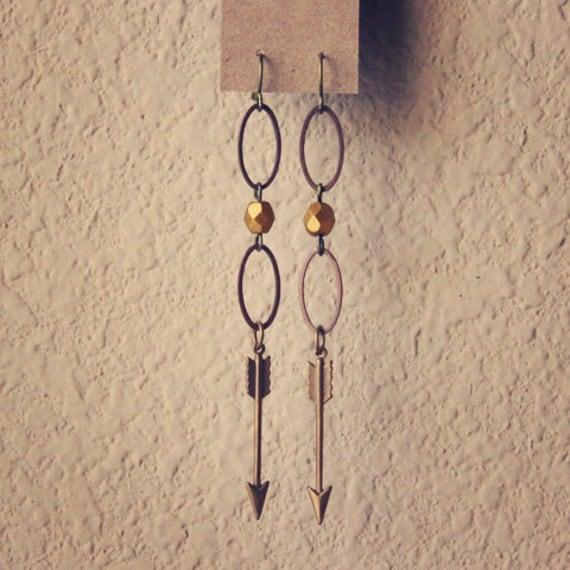 adela.  a pair of golden arrow earrings.