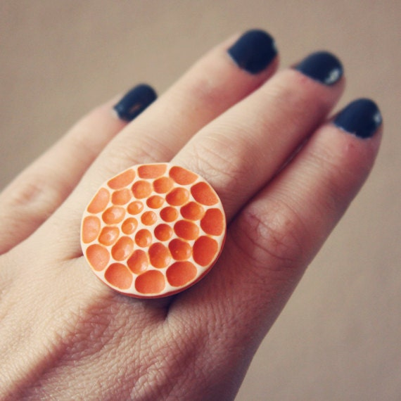 ami.  an orange honeycomb cab ring.
