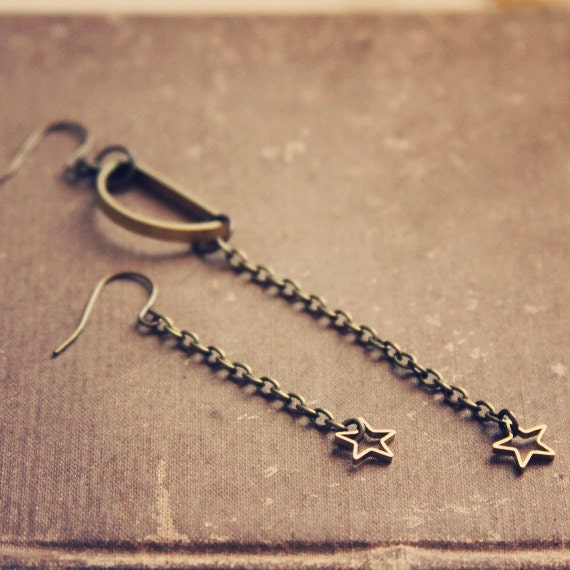 moonchild.  a pair of golden assymetrical moon and star earrings.