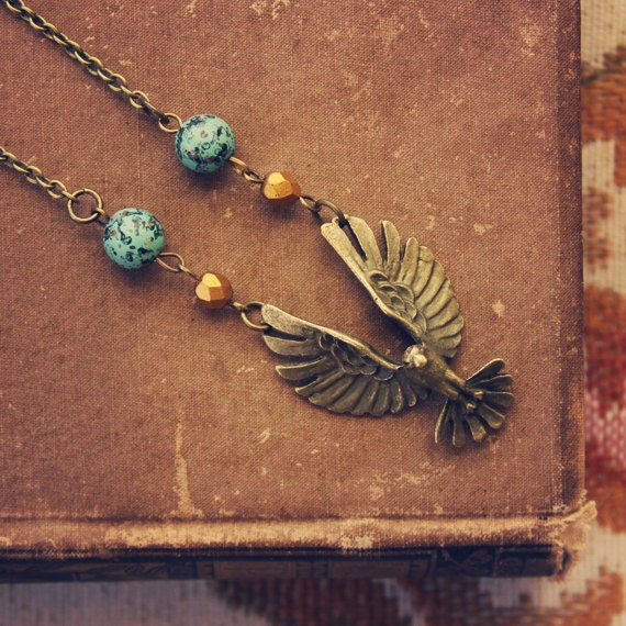 skylar.  a beaded brass bird in flight necklace.
