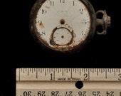 Found materials, weathered pocket watch,