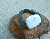 Dark grey rectangular beads bracelet with large white accent charm