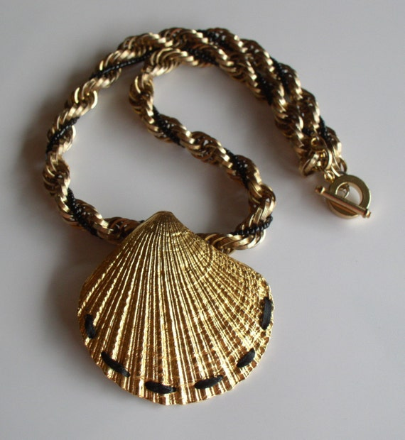 Gold toned shell shaped pendant with gold and black chain