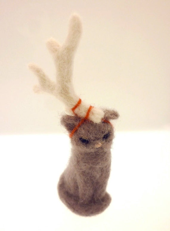 Needle felted sulky grey cat with a single white antler tied on its head for Christmas