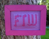 "Purple/magenta embroidered ""FTW"" wall hanging"