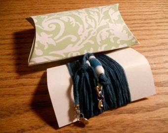 teal silk wrap bracelet with Hawaiian charm and silver dollar charms