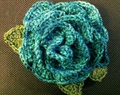 Blue-green crochet rose pin to raise money for Cystic Fibrosis research
