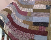 patchwork  quilt in stripes of blue burgundy and brown