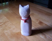 limestone cat with red beaded necklace collar