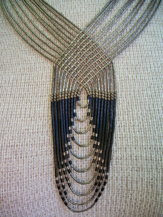 Tribal necklace, metallic and black beaded strands woven together in unique pattern.