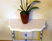 Vintage three legged table or wall shelf with pastel accents