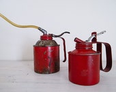 vintage pair of ruby red oil cans
