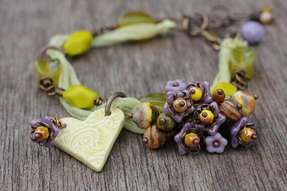 Wire wrapped beaded bracelet, czech glass flowers, Jasper rounds, brass chain, ceramic heart charm, green yellow tones lilac