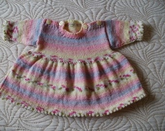 Hand knitted first size baby girls dress in soft pastel self striping yarn