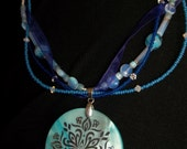 Multi-strand beaded necklace with ribbon and blue shell pendant