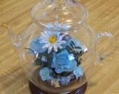 Vintage Blown Clear Glass Decorative Teapot with Enclosed Blue Silk Floral Arrangement on Attached Wooden Base