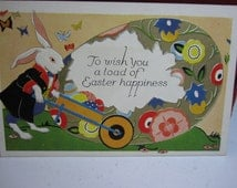 Art Deco 1920's embossed gold gilded easter greeting postcard dressed rabbit pushing wheelbarrow full of colored eggs and giant egg