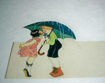 Adorable unused Art Deco 1920's-30's die cut place card little girl and Boy kissing Under umbrella
