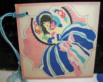 1920's Art Deco bridge tally card pretty girl holding a deco parasol with a fancy dress and hat buzza