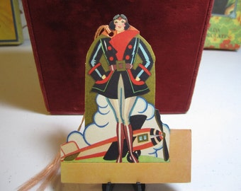1920's-30's unused art  deco die cut bridge tally place card aviation theme deco lady airplane pilot ,plane and cloudburst in background