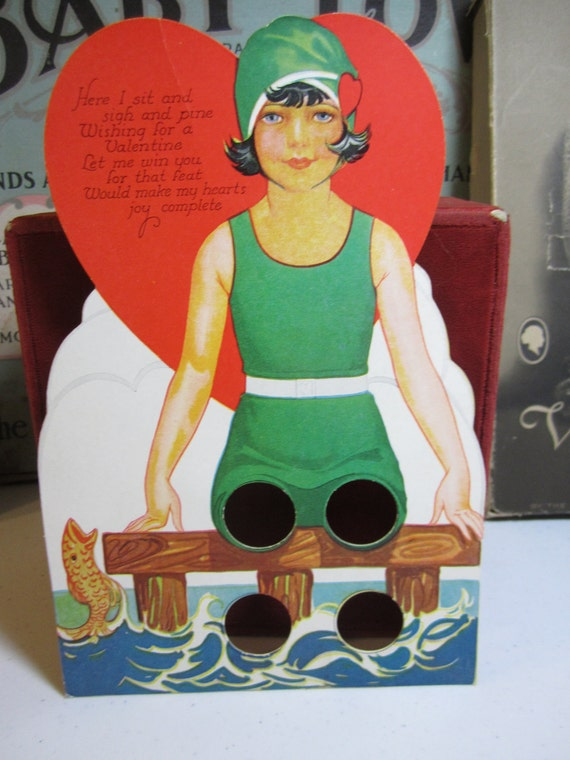 1930's large die cut  Carrington Valentines card girl with bobbed hair , swimsuit, cap sits on pier holes to put fingers through