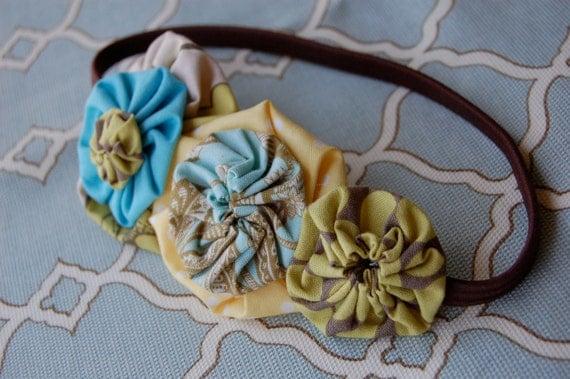 Six fabric yoyos on elastic headband