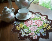 Round brown handkerchief or doily with pink roses