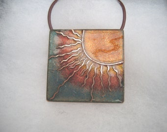 Enamelled pendant with sunburst in golds, reds and blues