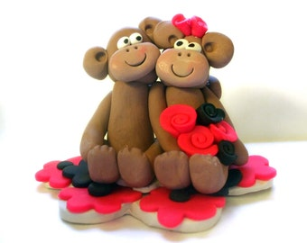 Wedding cake topper with monkeys and pink and black flowers