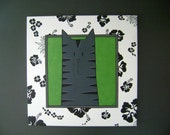 Original Acrylic Painting: Grey Cat on Green, framed with Black and White ribbon and painted Black and White Flowers