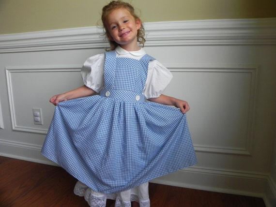 """Dorthy, Wizard of Oz Costume Apron and two hair bows. Chest measurement 23"""" to 27"""" for children."""