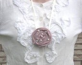 Rolled soft pink fabric flower with tiny pearls attached to white ribbon