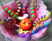 hand sculpted polymer rainbow octopus partially upcycled with lollipop.