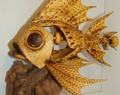 Mechanical fish with propeller when turned by hand opens mouth and moves front fins.  Carving has saw blade teeth.
