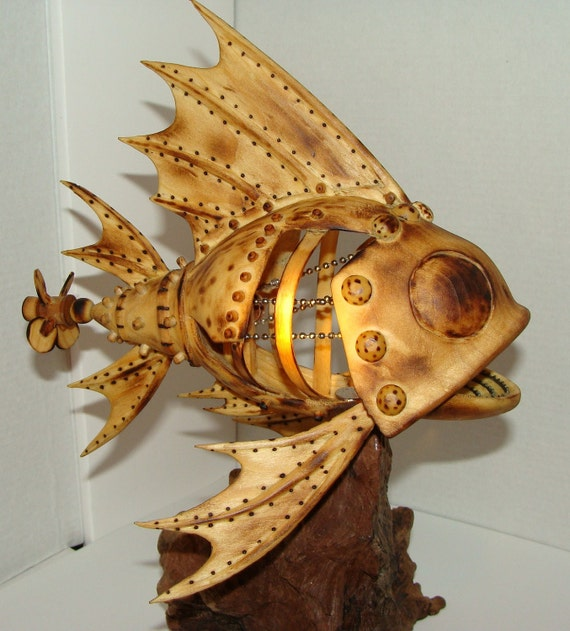 Hand carved Mechanical fish with propeller that turns by hand. Carving has chain inner parts and saw blade teeth.