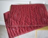 "Red cloth quilted placemats with stitched ""faux bois' woodgrain design, made from recycled fabric"