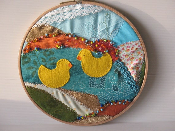 embroidery hoop, fibre art, fabric collage,  two yellow ducks swimming in a pond on a crazy quilt background -