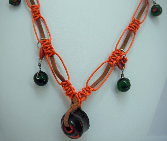 Orange knotted necklace with green glass beads, ceramic baubles and rubber loops around a leather strand