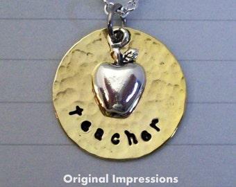 Closeout sale teacher pendant necklace of hammered brass decorated with a sterling silver apple charm on a silver-plated chain.
