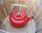 Fire engine red metal tea kettle with wooden handle and knob.