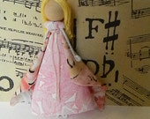 Fairy doll with blonde hair, long pink dress and cape