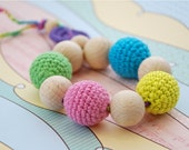 Teething toy with crochet wooden beads. Bright yellow, blue, pink, green, violet.