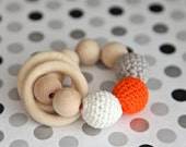 Teething toy with crochet wooden beads and 2 wooden rings. Light grey, bright orange, white wooden beads rattle.