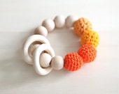 Orange, tangerine, pumpkin, deep carrot orange teething ring toy with crochet wooden beads. Rattle for baby.